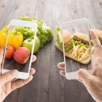 Friends using smartphones to take photos with contrasting food