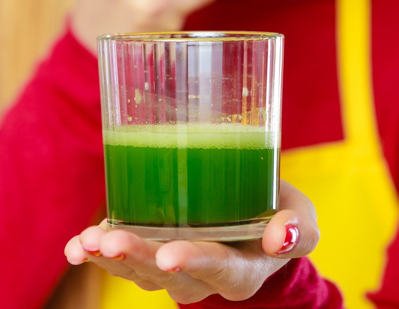 Drinks good for health, diet breakfast concept. Young woman in kitchen holding green healthy vegetable smoothie juice glass looking through magnifying glass