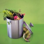 Silver compost bin with banana peels, carrot tops, apple core and other food scraps.