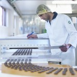 Worker inspecting chocolate on production line in chocolate factory